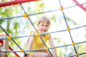 Beautiful girl climbing on rope ladder against sky