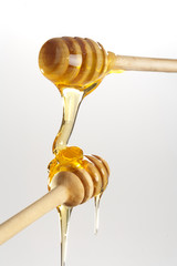 Honey dripping from a wooden honey dippers