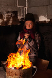 Poor beggar child warming up at the fire in a tin pot