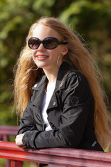Young girl with long blonde hair and sunglasses on bridge in par