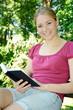Junge freundliche Frau liest Buch im Park auf Parkbank