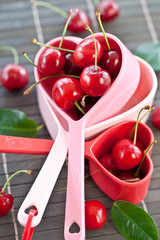 Fresh cherries in measuring cups