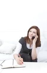 Frau telefoniert und macht sich Notizen