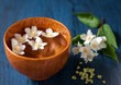 Spa. White flowers in a bowl of water on a vintage board