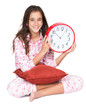 Girl wearing pajamas and holding a clock isolated on white