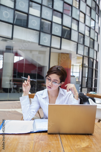 Attractive businesswoman working with laptop at cafe