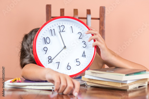 Tired student sleeping on her desk and holding a clock