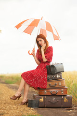 Redhead girl with suitcases at outdoor