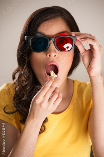 Shocked young woman watching 3D movie