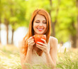 Redhead girl with orange cup at outdoor