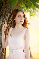 Redhead girl near tree at countryside