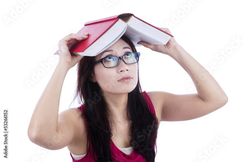 Afraid female student cover head with book - isolated