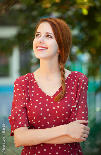 Redhead girl in red dress at outdoor near old house