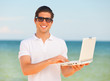 Handsome young man with laptop at beach background