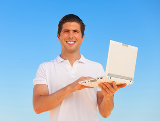 Handsome young man with laptop at blue sky background