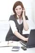 Frau am Notebook telefoniert