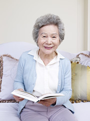 senior woman holding a book and smiling