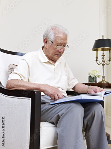 senior asian man reading a book at home
