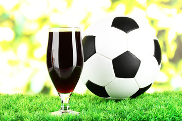 Glass of beer on lawn with ball