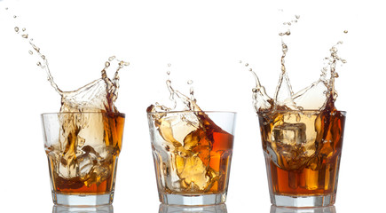 whiskey set splashing out of glass on white