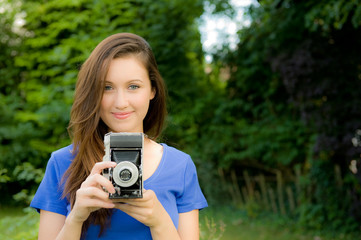 Young Woman Taking Photographs With Old Camera