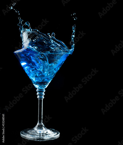 blue cocktail splashing into glass on black