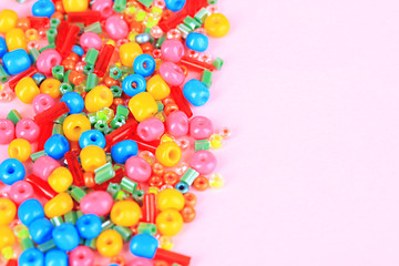 Different colorful beads on beige background