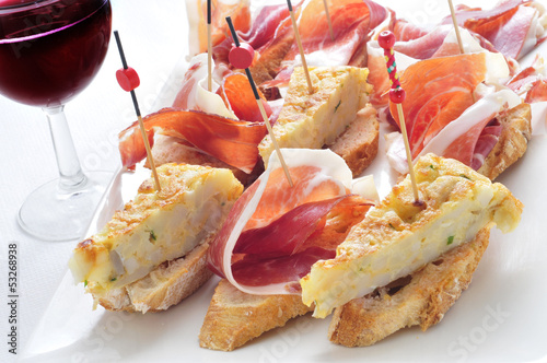 spanish pinchos, spanish tortilla and serrano ham served on brea