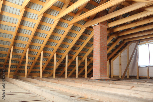Roof frame covered by profiled metal sheet and brick chimney