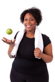 Overweight young black woman holding an apple - African people