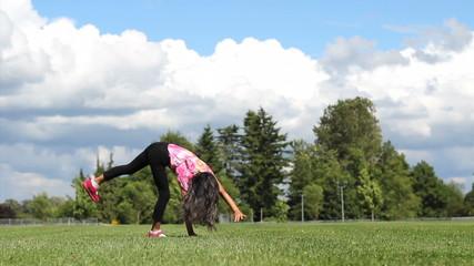 Cute Asian Girl Doing Cartwheels On The Grass