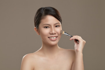 Female asian applying foundation