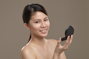 Female asian holding a mirror
