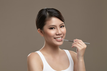 Female asian applying lipgloss