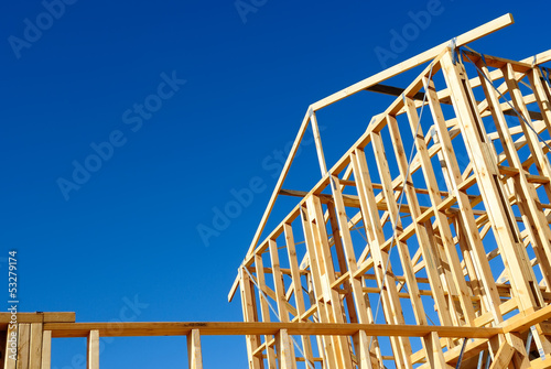 Wooden house frame against blue sky