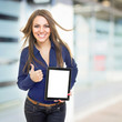 Positive young businesswoman with tablet computer