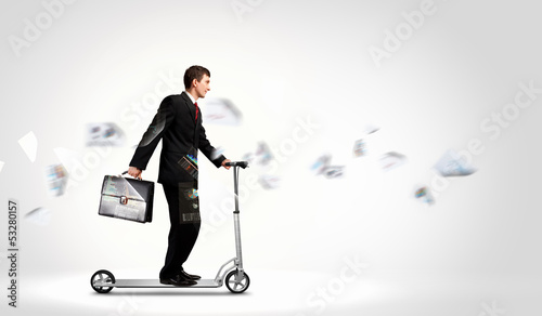 Businessman riding scooter