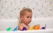 Little girl playing with toy dinosaurs in the bathtub