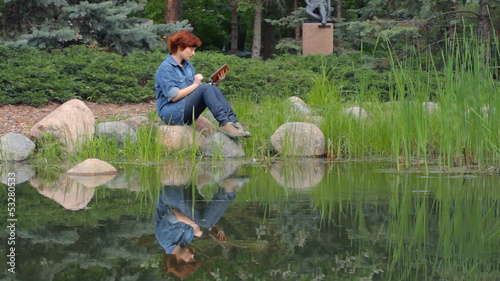 Red-haired girl sitting on the pond and read e-reader