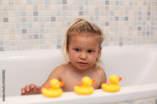 Little girl playing with rubber ducks in the bathtub