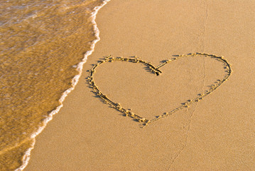 Heart shape drawing in the sand