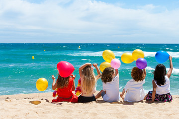 Children sitting on beach with color balloons.