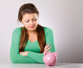 Young beautiful woman with piggy bank