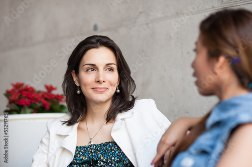 Two young female friends gossiping in a bar.
