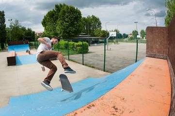 Skateboarder jumping in halfpipe at skatepark.