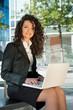 Business woman portrait outdoors using laptop.