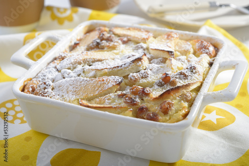 Apple flognarde with raisins and powdered sugar in a baking dish