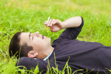 Boy with a cigarette lying in a meadow