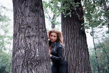 Woman posing between trees