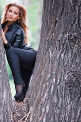 Woman posing on tree trunk